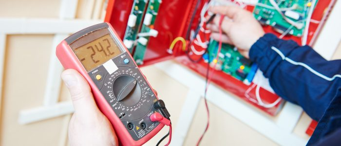 Electrical equipment. Electrician with tester multimeter in the hands measuring current voltage.
