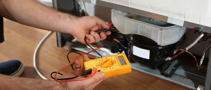 Male technician repairing broken refrigerator indoors, closeup